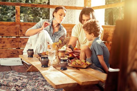 Healthy lifestyle. Delighted happy family talking to each other while enjoying their delicious healthy meal Stock Photo