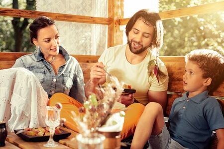 Pleasant conversation. Positive happy man eating food while speaking with his son Stock Photo