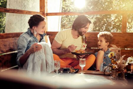 Happy family. Happy nice boy listening to his father while sitting at the table