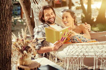 Favourite story. Positive nice woman looking into the book while lying together with her boyfriend