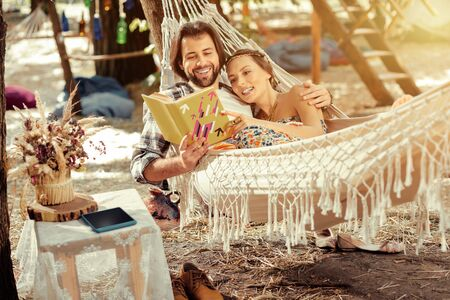 Best relaxation. Joyful nice couple reading a book while enjoying their rest together in a hammock