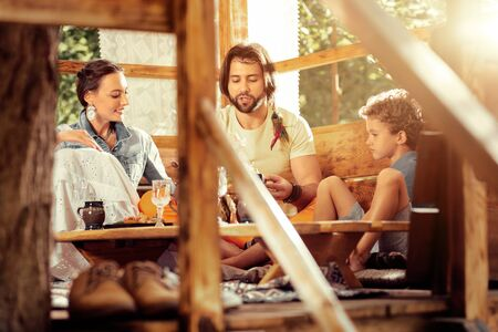 Pleasant communication. Positive nice family sitting around the table while speaking with each other Stock Photo