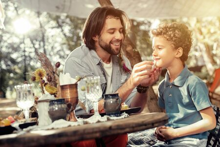 Father and son. Joyful positive man caring about his son while having breakfast with him Stock Photo
