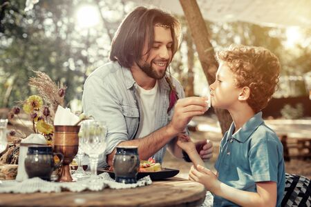 Caring father. Nice long haired man sitting with son while expressing his care