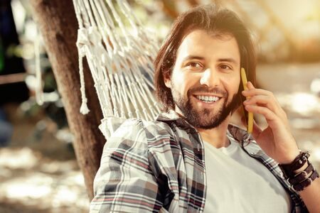Mobile connection. Delighted bearded man putting his phone to the ear while answering a phone call
