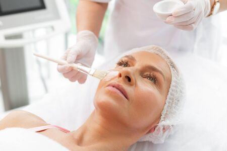 Strumenti di cosmetologia. Primo piano di un pennello in uso durante l'applicazione di una maschera facciale