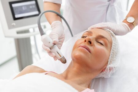 Durante el procedimiento. Agradable mujer madura acostada con los ojos cerrados mientras se realiza un procedimiento de elevación del cuello
