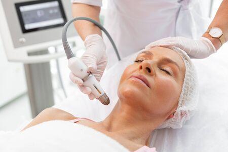 Pendant la procédure. Belle femme mature allongée les yeux fermés tout en ayant une procédure de levage du cou