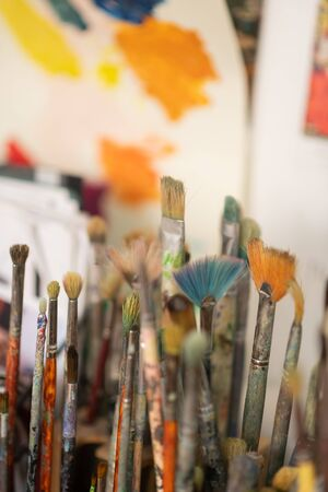 Painting brushes. Different painting brushes standing near the wall in light artistic workshop Archivio Fotografico