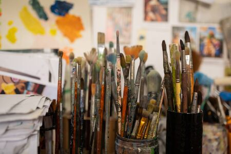 Different brushes. Different think and thick painting brushes standing in workshop of famous artists