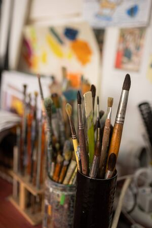 Brushes for painting. Close up of different brushes for painting standing on the table of famous artist