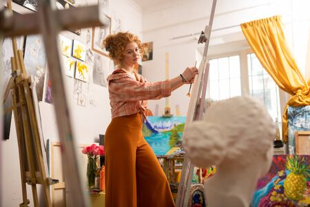 Painting near window. Red-haired artist having some inspiration painting on canvas standing near window
