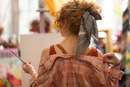 Cool hairstyle. Red-haired curly art student with cool hairstyle holding painting brush Stok Fotoğraf