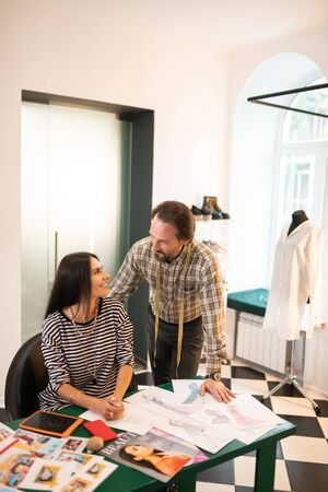 Having conversation. Cheerful contended joyful nice-looking smiling beaming dark-haired designers having a conversation during work at their office 免版税图像 - 126988726
