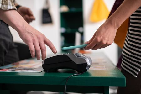 Paying via phone. Close-up shot of a customer attaching smartphone to the payment terminal for paying