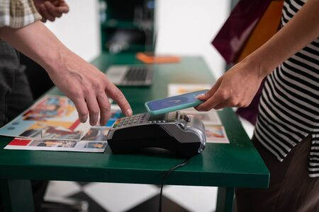 Paying via PayPass. Mug shot of a female attaching smartphone to the credit card terminal for paying via PayPass. Stock Photo