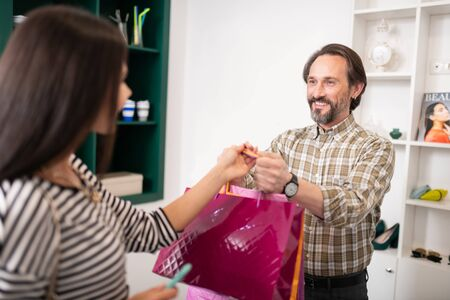 Handing packages. Happy contended mature dark-haired bearded customer handing the shopping packages with clothes to lovely alluring appealing woman.