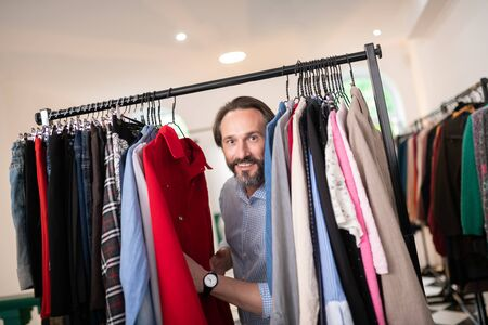 A man in the store. Close-up portrait of pleasing handsome nice-looking bearded dark-haired male in a blue checked shirt pushing clothes in the clothing store.