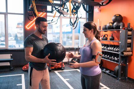 Dare palla fitness. Un bell'allenatore barbuto che dà la palla fitness al suo cliente con un leggero sovrappeso