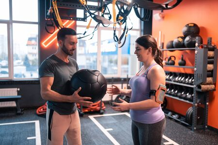 Giving fitness ball. Bearded handsome trainer giving fitness ball to his client with slight overweight
