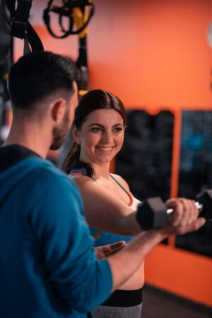 Woman smiling. Dark-haired plump woman smiling while talking to trainer and doing exercises
