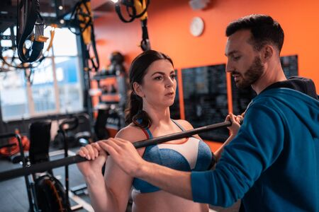 Woman working out. Dark-haired woman working out with barbell near her handsome bearded trainer