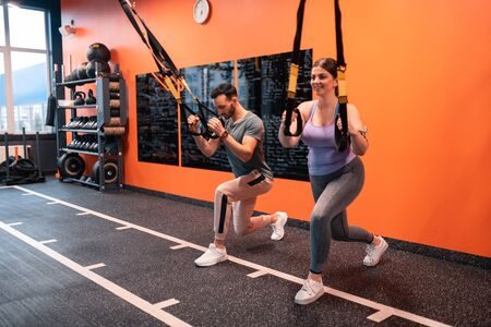 Lunging forward. Trainer and his client with overweight lunging forward holding straps