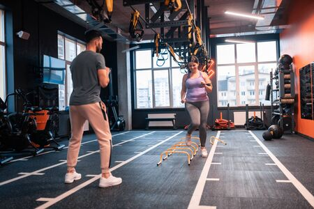 Obstacle race. Overweight woman in sport clothing having obstacle race in gym with her trainer