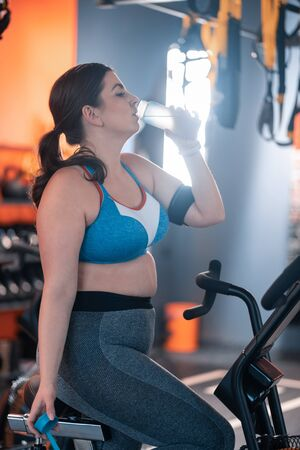 Water while cycling. Dark-haired overweight woman wearing short top drinking water while cycling in gym