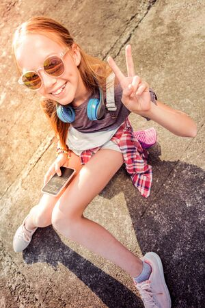 Entertaining with smartphone. Cheerful young girl in sunglasses being in great mood while staying outside and chatting in a smartphone