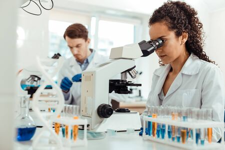 Serious work. Smart female biologist looking into the microscope while doing her work Фото со стока
