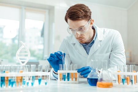 Protective equipment. Serious handsome scientist wearing special protective glasses while working in the chemical lab