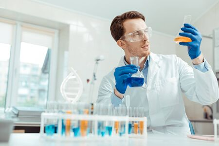 Professional chemist. Nice handsome man holding two different flasks while working in the chemical lab Banco de Imagens