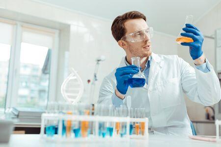 Professioneller Chemiker. Netter gutaussehender Mann, der zwei verschiedene Flaschen hält, während er im Chemielabor arbeitet Standard-Bild
