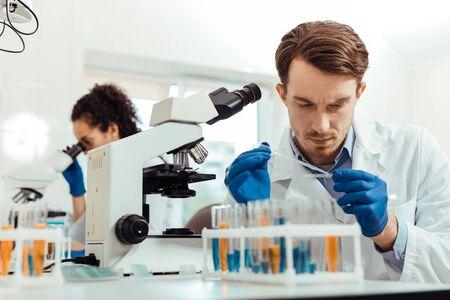 Biologisches Labor. Kluger junger Mann, der im Labor arbeitet, während er als Biologe arbeitet