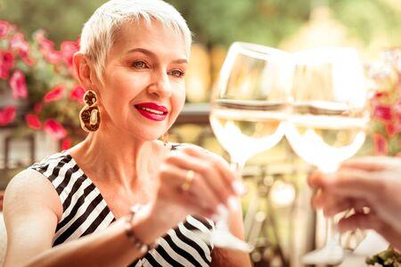 Wearing massive earrings. Mature woman wearing massive earrings drinking wine with husband