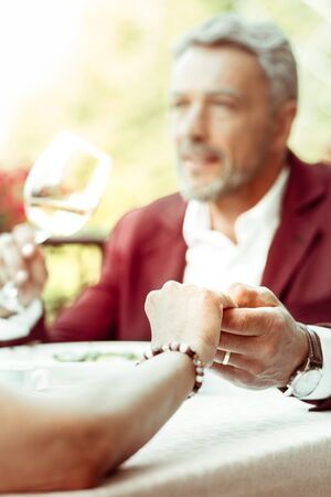 Wife touching hand. Wife wearing bracelet touching hand of her handsome bearded man while having dinner