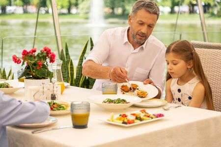 Snacks for girl. Grey-haired bearded granddad giving his cute girl some snacks with salmon