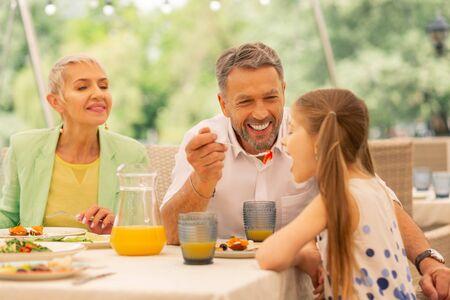 Feeding cute girl. Beaming grey-haired bearded granddad feeding his lovely cute girl