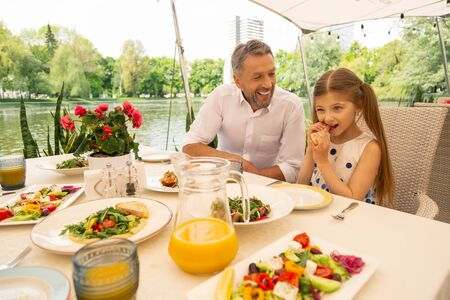 Grandfather smiling. Grey-haired grandfather smiling looking at girl eating bruschetta having breakfast outside