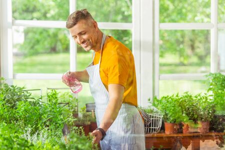 Giving water. Smiling man standing near windows of his flower shop and sprinkling plants.