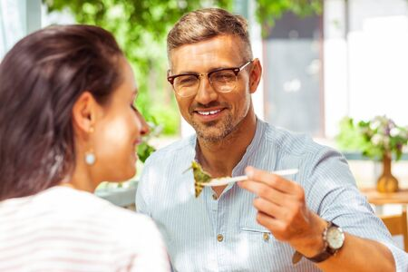 Sharing is caring. Smiling man giving his wife a fork with a piece of his dish at a summer cafe. Stock Photo