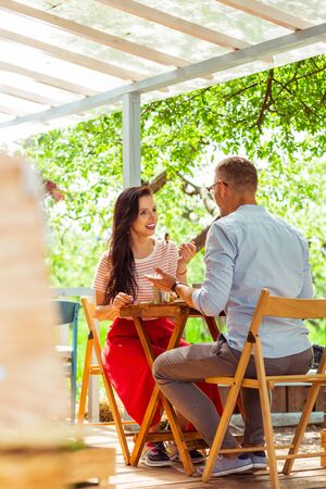 Summer date. Two happy beutiful people having a date on a summer terrace of a cafe.
