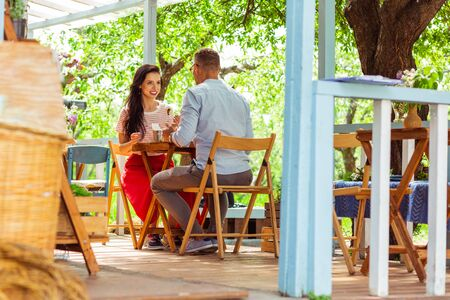 Having lunch together. Happy couple talking and eating together in a spacious summer cafe.