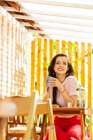 Morning coffee. Pretty smiling woman drinking coffee and waiting for a friend in the summer cafe. Stock Photo