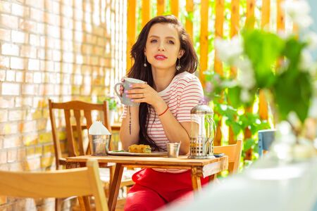 Before work. Thoughtful woman spending her morning sitting at the table of a summer cafe. Stock Photo