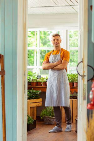 Serving customers. Handsome flower shop seller smiling to his customers standing behind the doorway.