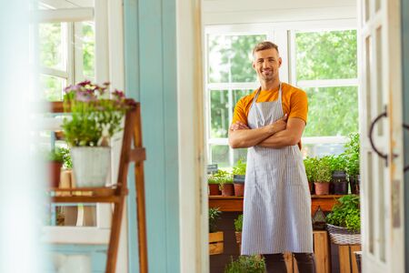 Waiting on trade. Smiling plantsman standing in the middle of the flower shop waiting for buyers. Stock Photo