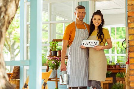 Business partners. Smiling couple standing on the porch of the flower shop they are opening. Stock Photo