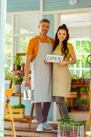 Starting business. Happy couple holding an open sign standing near their new flower shop.